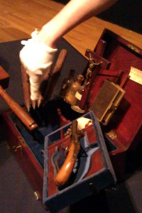 A museum employee points out interesting features of the Vampire Killing Kit